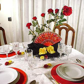 table setting idea for a Spanish dinner party. The centerpiece is made with a fan, mantilla and roses